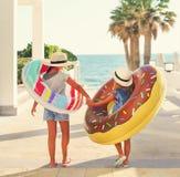 Δύο μικρά κορίτσια με τα διογκώσιμα παιχνίδια στην παραλία Στοκ Εικόνες