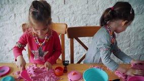 Δύο μικρά κορίτσια παίζουν με την κινητική άμμο στον πίνακα απόθεμα βίντεο
