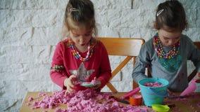 Δύο μικρά κορίτσια παίζουν με την κινητική άμμο στον πίνακα φιλμ μικρού μήκους