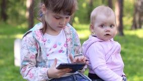 Δύο μικρά κορίτσια παίζουν με το PC ταμπλετών απόθεμα βίντεο