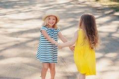 Δύο μικρά κορίτσια περιστρέφουν τα χέρια εκμετάλλευσης Στοκ εικόνα με δικαίωμα ελεύθερης χρήσης