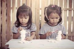 Δύο μικρά κορίτσια που έχουν τη διασκέδαση για να χρωματίσει στην κούκλα στόκων Στοκ φωτογραφία με δικαίωμα ελεύθερης χρήσης