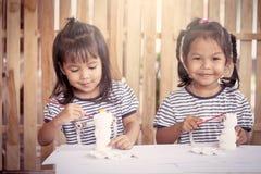 Δύο μικρά κορίτσια που έχουν τη διασκέδαση για να χρωματίσει στην κούκλα στόκων Στοκ Εικόνα