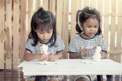 Δύο μικρά κορίτσια που έχουν τη διασκέδαση για να χρωματίσει στην κούκλα στόκων Στοκ Φωτογραφίες