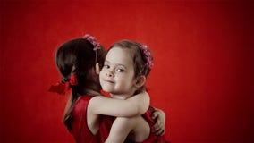 Δύο μικρά κορίτσια που αγκαλιάζουν σε ένα κόκκινο υπόβαθρο απόθεμα βίντεο