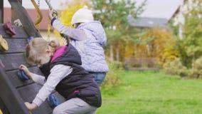 Δύο μικρά κορίτσια που αναρριχούνται στον τοίχο στην παιδική χαρά απόθεμα βίντεο