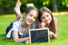 Δύο μικρά κορίτσια που θέτουν στη χλόη με τον κενό πίνακα κιμωλίας Στοκ φωτογραφία με δικαίωμα ελεύθερης χρήσης