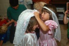 Δύο μικρά κορίτσια που ντύνουν επάνω στις γαμήλιες εξαρτήσεις στοκ φωτογραφία