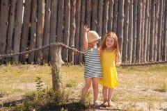 Δύο μικρά κορίτσια που στέκονται στο φράκτη Στοκ φωτογραφίες με δικαίωμα ελεύθερης χρήσης