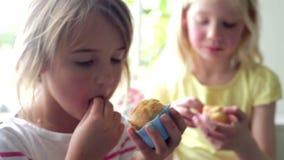 Δύο μικρά κορίτσια που τρώνε Cupcakes από κοινού απόθεμα βίντεο