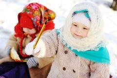 Δύο μικρά κορίτσια στα ρωσικά σάλια ενάντια στο σκηνικό του s Στοκ Εικόνες