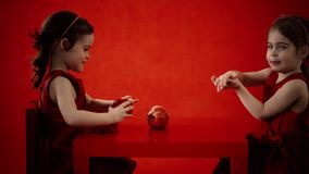 Δύο μικρά κορίτσια τρώνε τα μήλα σε έναν κόκκινο πίνακα απόθεμα βίντεο