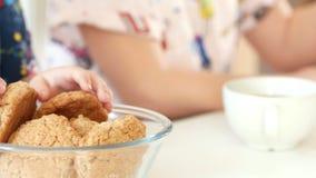 Δύο μικρά κορίτσια χύνουν το τσάι φρούτων στα φλυτζάνια με το ψήσιμο των σπιτικών μπισκότων φιλμ μικρού μήκους