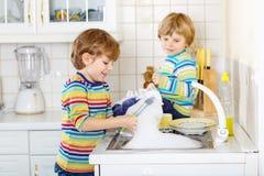 Δύο μικρά ξανθά αγόρια παιδιών που πλένουν τα πιάτα στην εσωτερική κουζίνα Στοκ Εικόνες