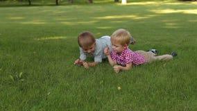Δύο μικρά παιδιά βρίσκονται στη χλόη στο πάρκο, σχίζουν από τη χλόη και την πετούν απόθεμα βίντεο