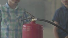 Δύο μικρά παιδιά με τα βρώμικα πρόσωπα και στα προστατευτικά κράνη που εξετάζουν τον πυροσβεστήρα με την έννοια ενδιαφέροντος φιλμ μικρού μήκους