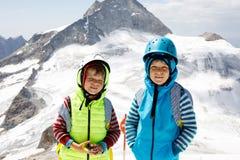 Δύο μικρά παιδιά με τα κράνη ασφάλειας και ιματισμός με τα υπόβαθρα τοπίων βουνών Παιδιά που και που ανακαλύπτουν Στοκ Εικόνα