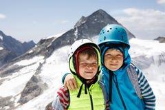 Δύο μικρά παιδιά με τα κράνη ασφάλειας και ιματισμός με τα υπόβαθρα τοπίων βουνών Παιδιά που και που ανακαλύπτουν Στοκ φωτογραφία με δικαίωμα ελεύθερης χρήσης