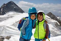 Δύο μικρά παιδιά με τα κράνη ασφάλειας και ιματισμός με τα υπόβαθρα τοπίων βουνών Παιδιά που και που ανακαλύπτουν Στοκ Εικόνες
