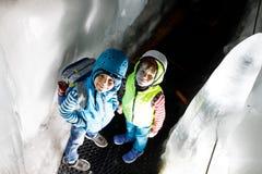 Δύο μικρά παιδιά με τα κράνη ασφάλειας και ιματισμός με τα υπόβαθρα τοπίων βουνών Παιδιά που και που ανακαλύπτουν Στοκ εικόνα με δικαίωμα ελεύθερης χρήσης
