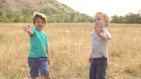 Δύο μικρά παιδιά που κυματίζουν τα χέρια τους στο ηλιοβασίλεμα φιλμ μικρού μήκους