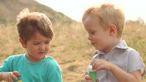 Δύο μικρά παιδιά που παίζουν με τις φυσαλίδες σαπουνιών στο πάρκο απόθεμα βίντεο