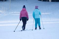Δύο μικρά παιδιά που τρώνε στον περίπατο στο χειμερινό πάρκο στοκ εικόνες
