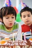 Δύο μικρά παιδιά που φυσούν τα κεριά στο κέικ Στοκ φωτογραφία με δικαίωμα ελεύθερης χρήσης