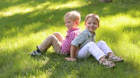 Δύο μικρά παιδιά 4 χρονών κάθονται πλάτη με πλάτη στο πάρκο στη χλόη απόθεμα βίντεο