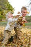 Δύο μικρά παιδιά που ρίχνουν τα φύλλα πτώσης έξω Στοκ Φωτογραφίες