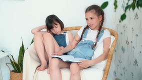 Δύο μικρά χαριτωμένα κορίτσια κάθονται στην καρέκλα, ένα από τα λέει το παραμύθι, σε αργή κίνηση απόθεμα βίντεο