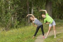 Δύο μικρά χαριτωμένα κορίτσια που θερμαίνουν υπαίθρια στοκ φωτογραφία με δικαίωμα ελεύθερης χρήσης