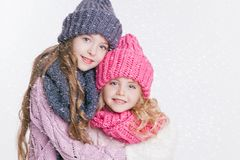 Δύο μικρές αδελφές που αγκαλιάζουν στα χειμερινά ενδύματα Καπέλα και μαντίλι γκρίζο ροζ Οικογένεια Χειμώνας Στοκ Εικόνα