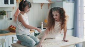 Δύο μικρές αδελφές που μαγειρεύουν στην κουζίνα, που επισύρει την προσοχή με το αλεύρι στον πίνακα, σε αργή κίνηση απόθεμα βίντεο