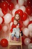 Δύο μικρές αδελφές με τα κόκκινα και άσπρα μπαλόνια Στοκ Φωτογραφίες