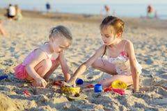 Δύο μικρές αδελφές που έχουν τη διασκέδαση σε μια παραλία Στοκ Φωτογραφίες