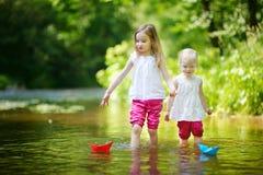 Δύο μικρές αδελφές που παίζουν με τις βάρκες εγγράφου στοκ φωτογραφίες με δικαίωμα ελεύθερης χρήσης