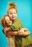 Δύο μικρές κόκκινες διευθυνμένες αδελφές κοριτσιών αγκαλιάζουν η μια την άλλη θερμά, τη σαφή ειλικρινή σχέση της αγάπης και την π στοκ εικόνα με δικαίωμα ελεύθερης χρήσης