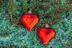 Δύο μικρές κόκκινες καρδιές γυαλιού με τις ζωηρόχρωμες διακοσμήσεις Χριστουγέννων ουράνιων τόξων και ένα μικρό πράσινο δέντρο έλα στοκ εικόνες