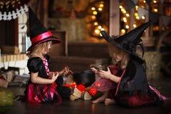 Δύο μικρές μάγισσες στα κοστούμια και τα καπέλα δημιουργούν το δοχείο, παιδική ηλικία Στοκ Φωτογραφίες