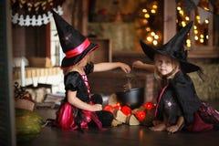 Δύο μικρές μάγισσες στα κοστούμια και τα καπέλα δημιουργούν το δοχείο, παιδική ηλικία Στοκ φωτογραφίες με δικαίωμα ελεύθερης χρήσης