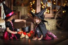 Δύο μικρές μάγισσες στα κοστούμια και τα καπέλα δημιουργούν το δοχείο, παιδική ηλικία Στοκ φωτογραφία με δικαίωμα ελεύθερης χρήσης