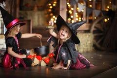 Δύο μικρές μάγισσες στα κοστούμια και τα καπέλα δημιουργούν το δοχείο, παιδική ηλικία Στοκ Εικόνες