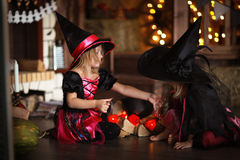 Δύο μικρές μάγισσες στα κοστούμια και τα καπέλα δημιουργούν το δοχείο, παιδική ηλικία Στοκ Φωτογραφία