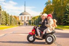 Δύο μικρές όμορφες αδελφές που κάθονται στο παιχνίδι Στοκ Εικόνες