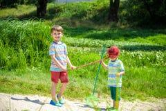 Δύο μικροί αδελφοί αμφιθαλών που παίζουν με το σέσουλα-δίχτυ στο λιβάδι Στοκ φωτογραφίες με δικαίωμα ελεύθερης χρήσης