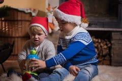 Δύο μικροί αμφιθαλείς στα καπέλα santa που παίζουν κοντά στην εστία στοκ φωτογραφίες