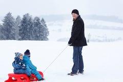 Δύο μικροί αμφιθαλείς και ο πατέρας τους που έχουν τη διασκέδαση στο έλκηθρο κερδίζουν επάνω Στοκ Εικόνες