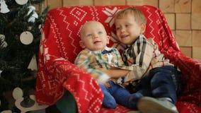 Δύο μικροί αδελφοί που κάθονται σε μια καρέκλα στο στούντιο απόθεμα βίντεο