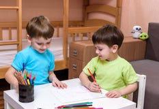 Δύο μικροί καυκάσιοι φίλοι που παίζουν με τα μέρη των ζωηρόχρωμων πλαστικών φραγμών εσωτερικών Ενεργά αγόρια παιδιών, αμφιθαλείς  Στοκ Εικόνες